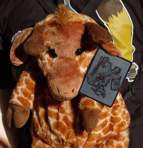 Giraffe plush backpack with a rectangular metal eartag that has a grayscale portrait of the giraffe