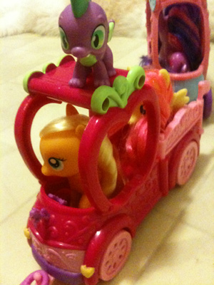 Spike standing on a pink truck in which are Applejack and Fluttershy