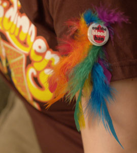 Rainbow feathers in button against brown shirtsleeve
